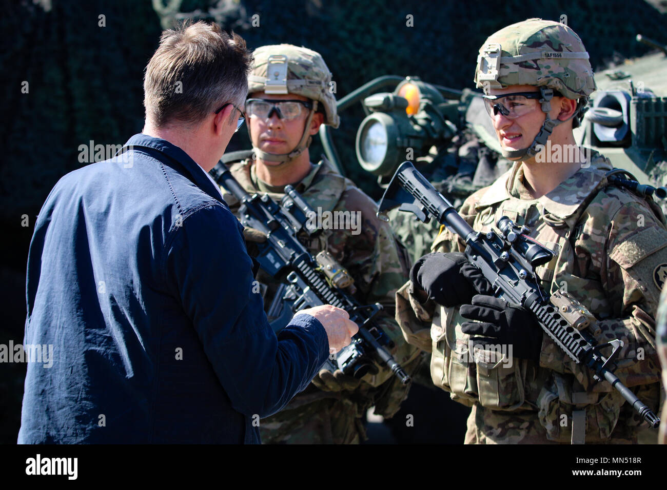 Spc. Michael Hacholski (right), and Pfc. Aidan Flodin (left), infantrymen with the 1st Squadron, 2nd Cavalry Regiment, talk with a student from the Baltic Defense College during an educational visit to Bemowo Piskie Training Area, Poland, May 8, 2018. Battle Group Poland is a unique, multinational coalition of U.S., U.K., Croatian and Romanian Soldiers who serve with the Polish 15th Mechanized Brigade as a deterrence force in support of NATO's Enhanced Forward Presence. (U.S. Army photo by Spc. Hubert D. Delany III /22nd Mobile Public Affairs Detachment) Stock Photo