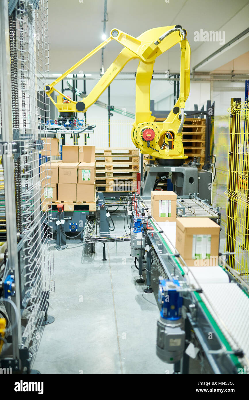 Interior of plant warehouse: industrial picking robot at work, cardboard boxes on conveyor belt, no people - Stock Image