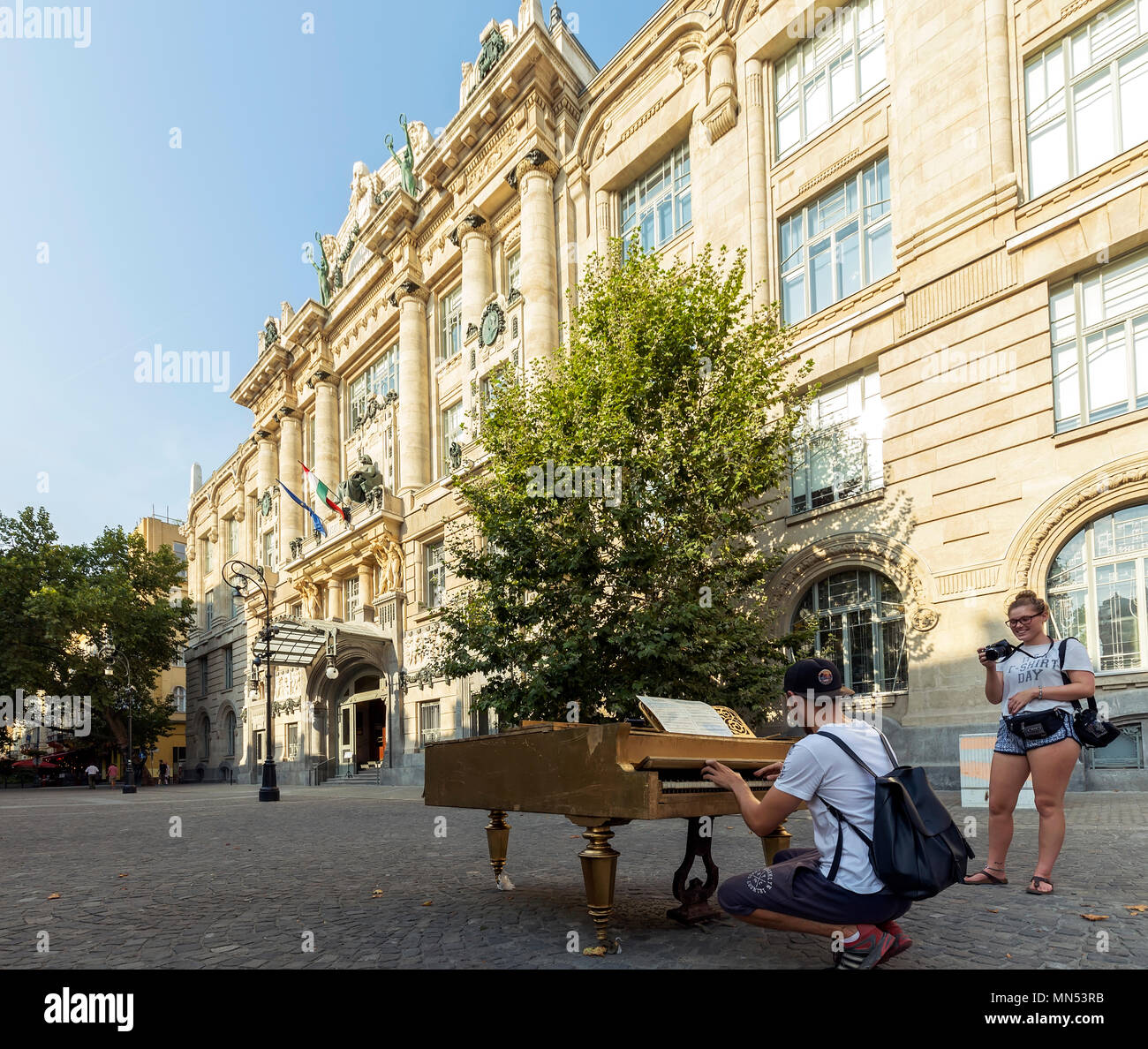 A working old gilded piano set up in joy of passers-by in front of the Liszt Ferenc Academy of Music's entrance. - Stock Image