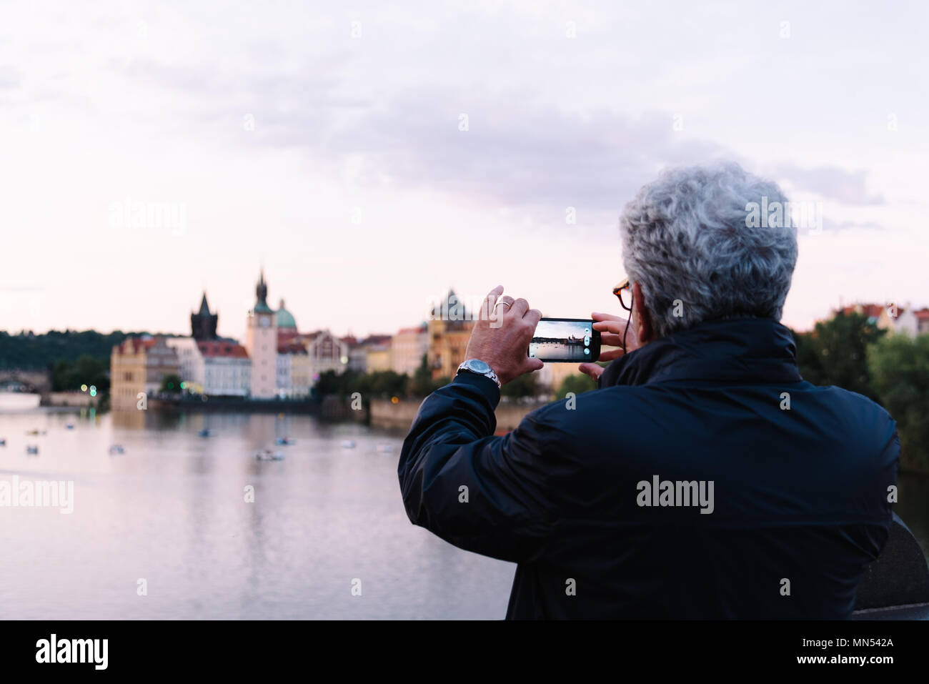 Prague,  Czech Republic - August 19, 2017: Unidentified man taking a photo of Prague at sunset - Stock Image