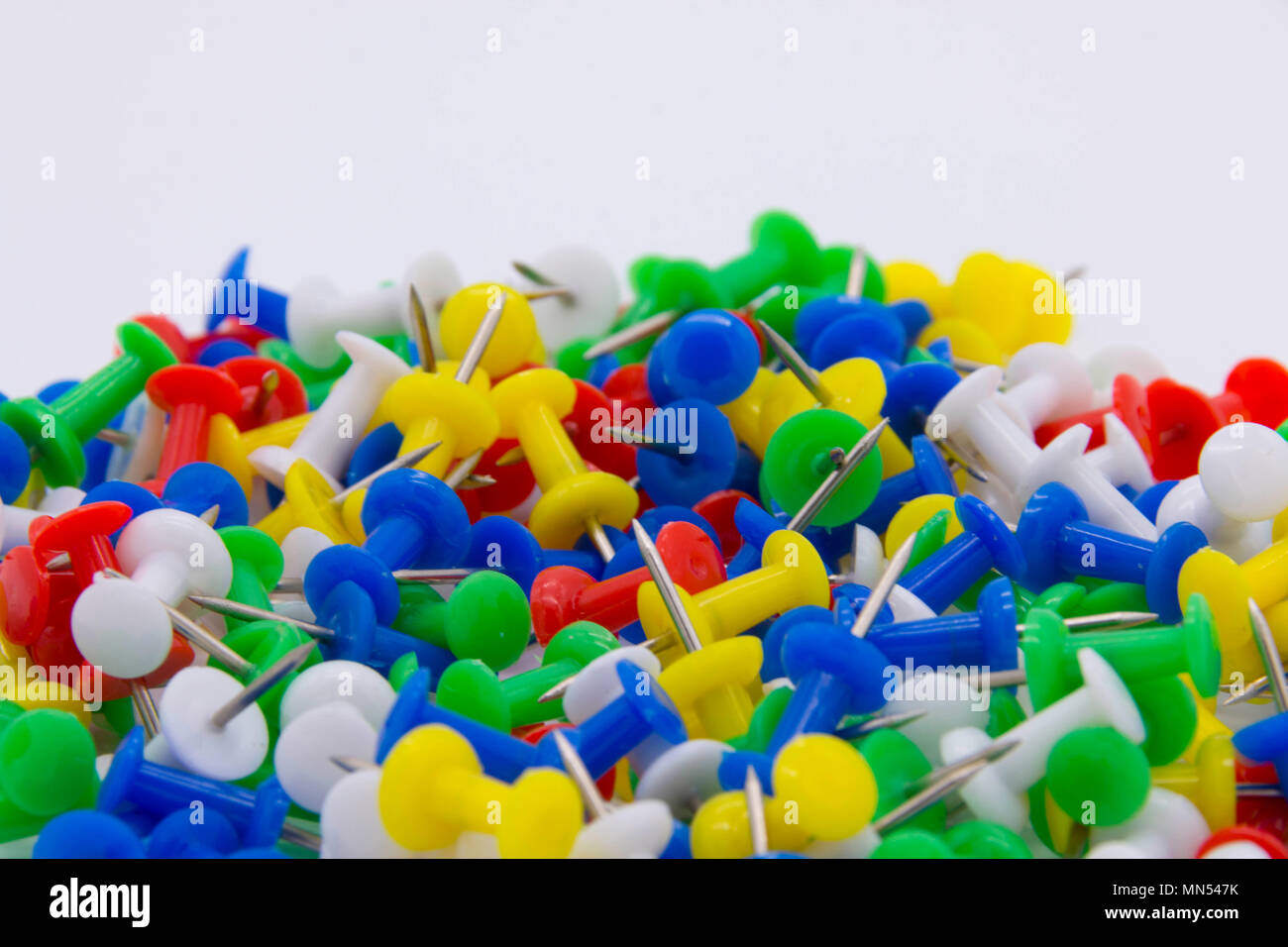 Pile of plastic notice board push pins on a white background - Stock Image