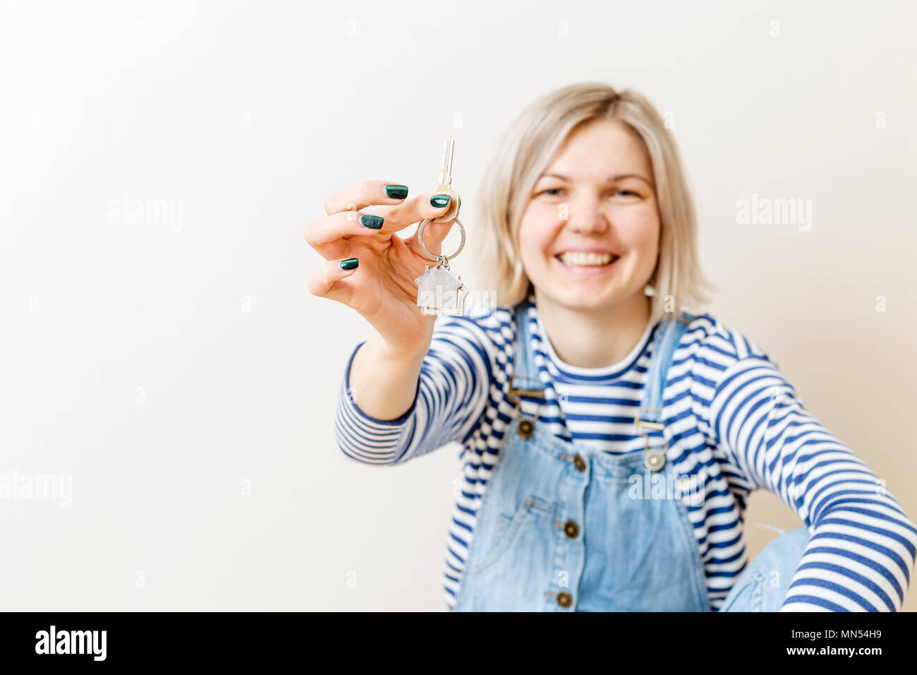 Photo of woman with keys from apartment against blank wall - Stock Image