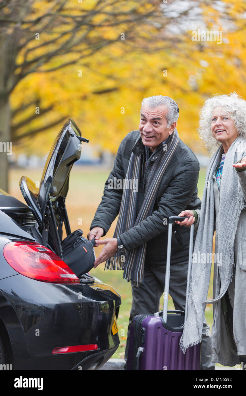 Senior couple removing luggage from car trunk - Stock Image