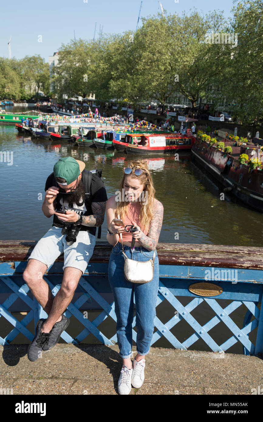 A tattooed couple absorbed in texting on the banks of the Grand Union Canal in Little Venice, London, UK - Stock Image