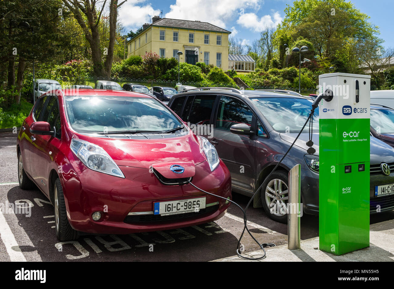 Electric car being charged in a car park in Skibbereen, County Cork, Ireland. - Stock Image