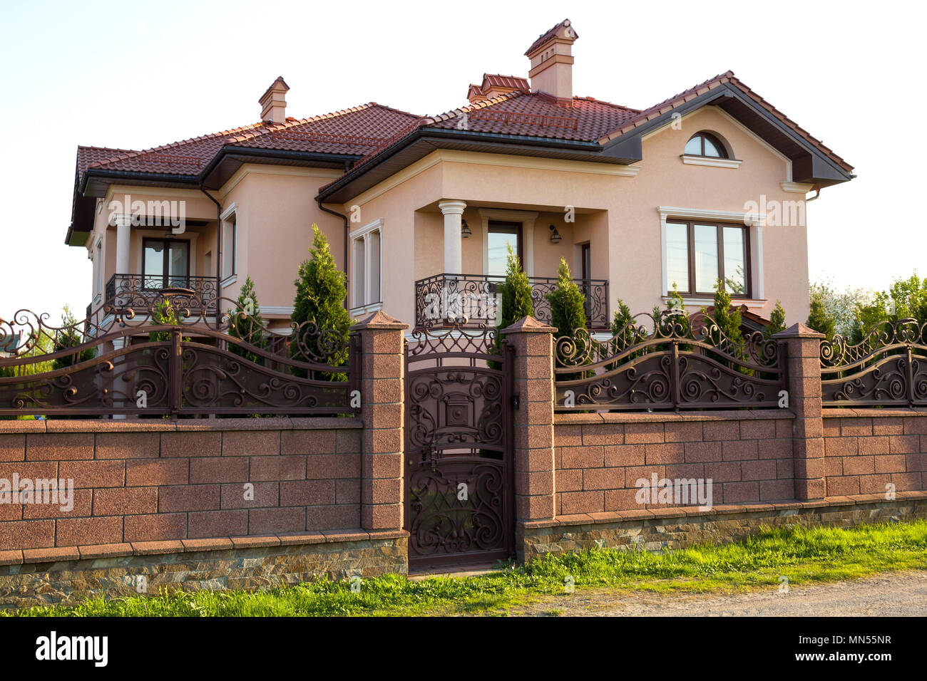 New Modern Luxurious Expensive Residential Two Story Cottage House With Shingle Roof Big Windows And Balconies Behind Stone Fence Iron Forged Ga