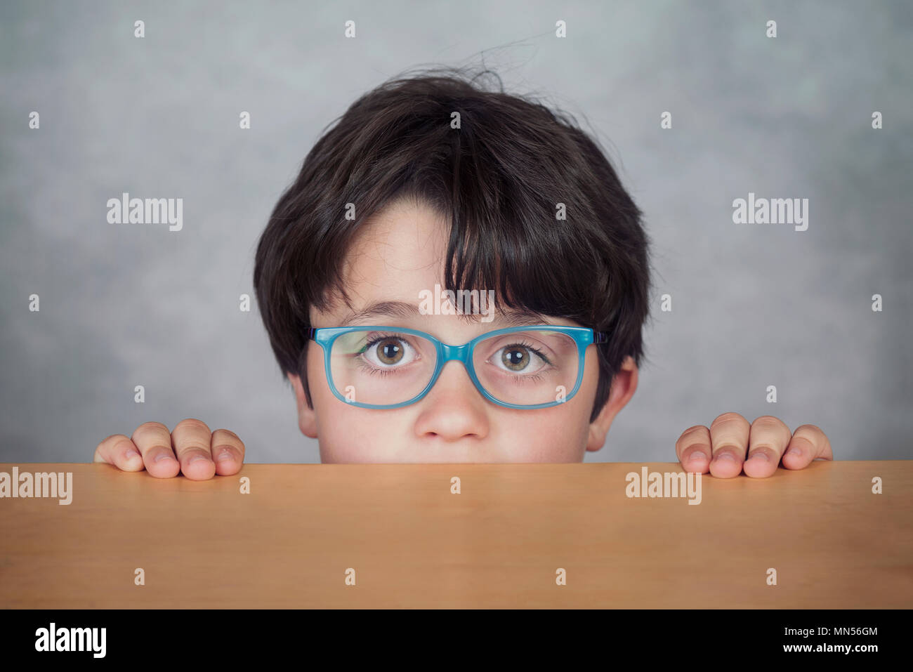 boy with glasses on a wooden table on gray background - Stock Image