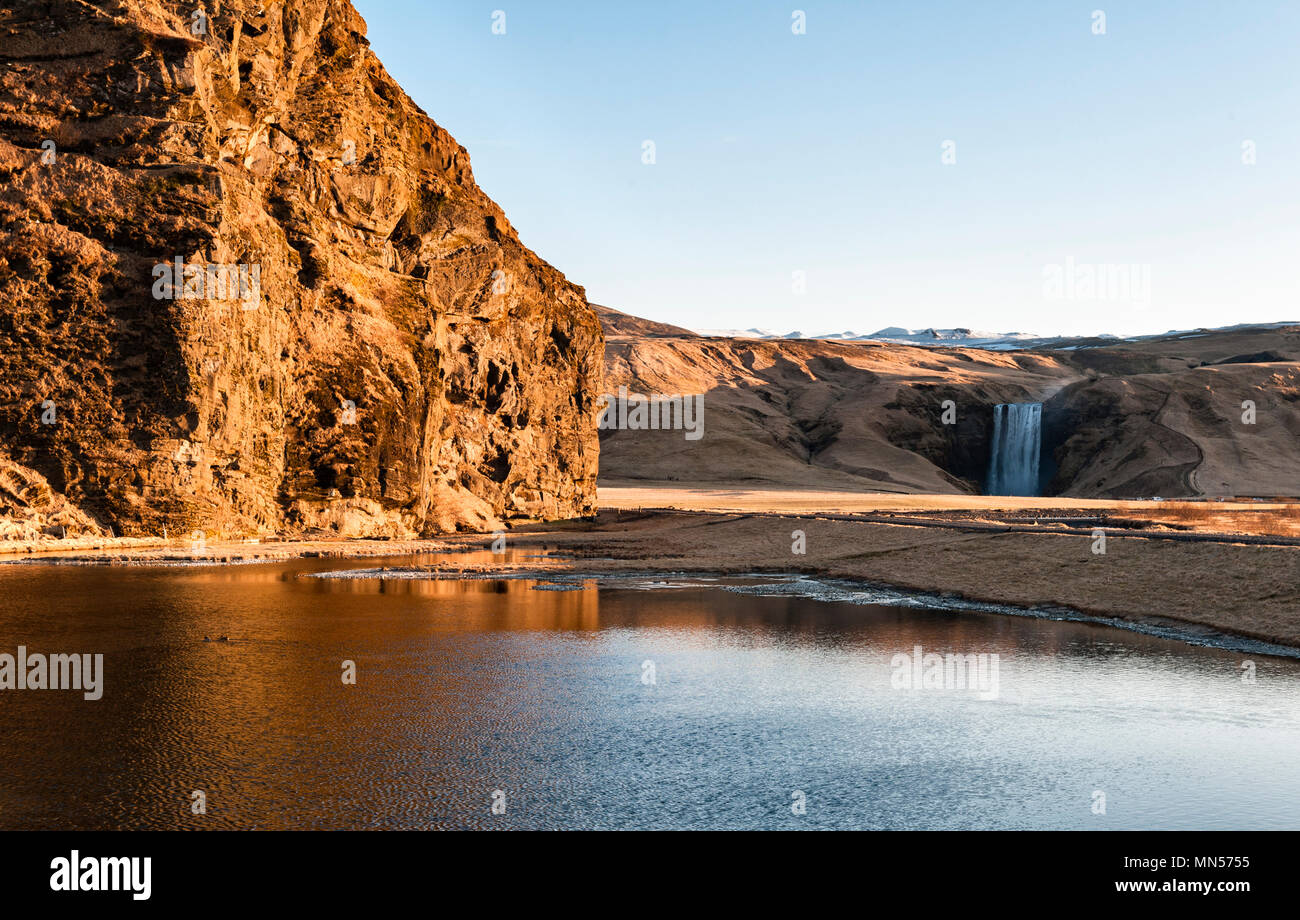 Skógar, south Iceland. A view at sunrise across the Skógá river, just downstream from the  Skógafoss waterfall (in the background) - Stock Image
