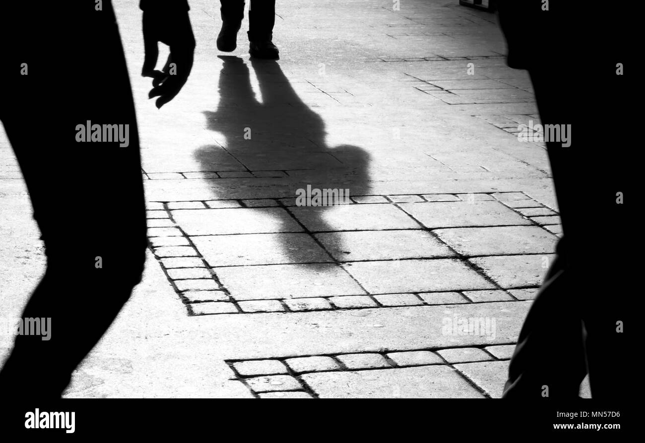 Shadow silhouette of two person on city sidewalk in black and white - Stock Image