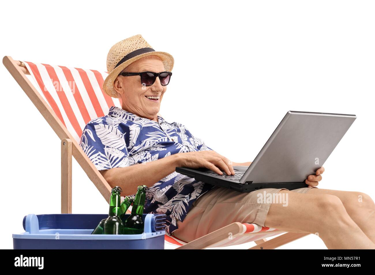 Elderly tourist with a laptop sitting in a deck chair next to a cooling box filled with bottles of beer isolated on white background Stock Photo