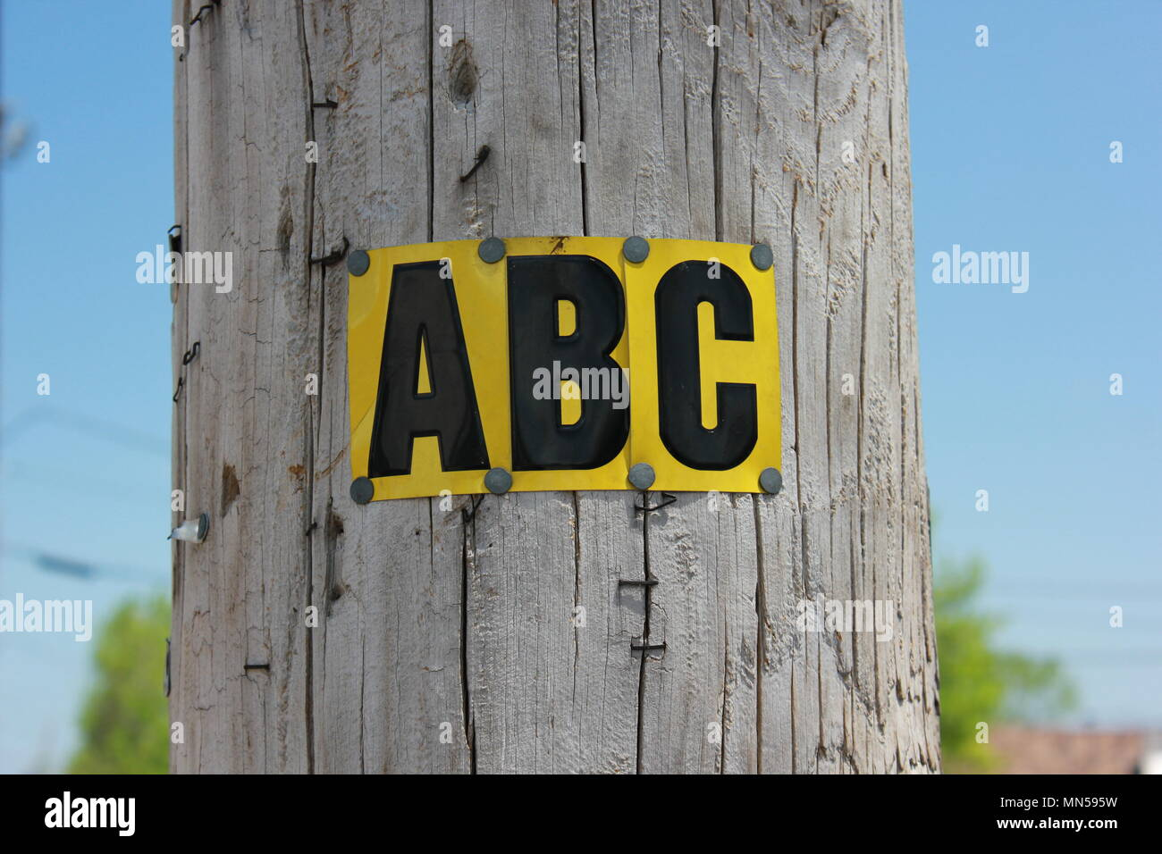 The capital letters a,b,and c stenciled on metal plates and nailed to a wooden post. - Stock Image