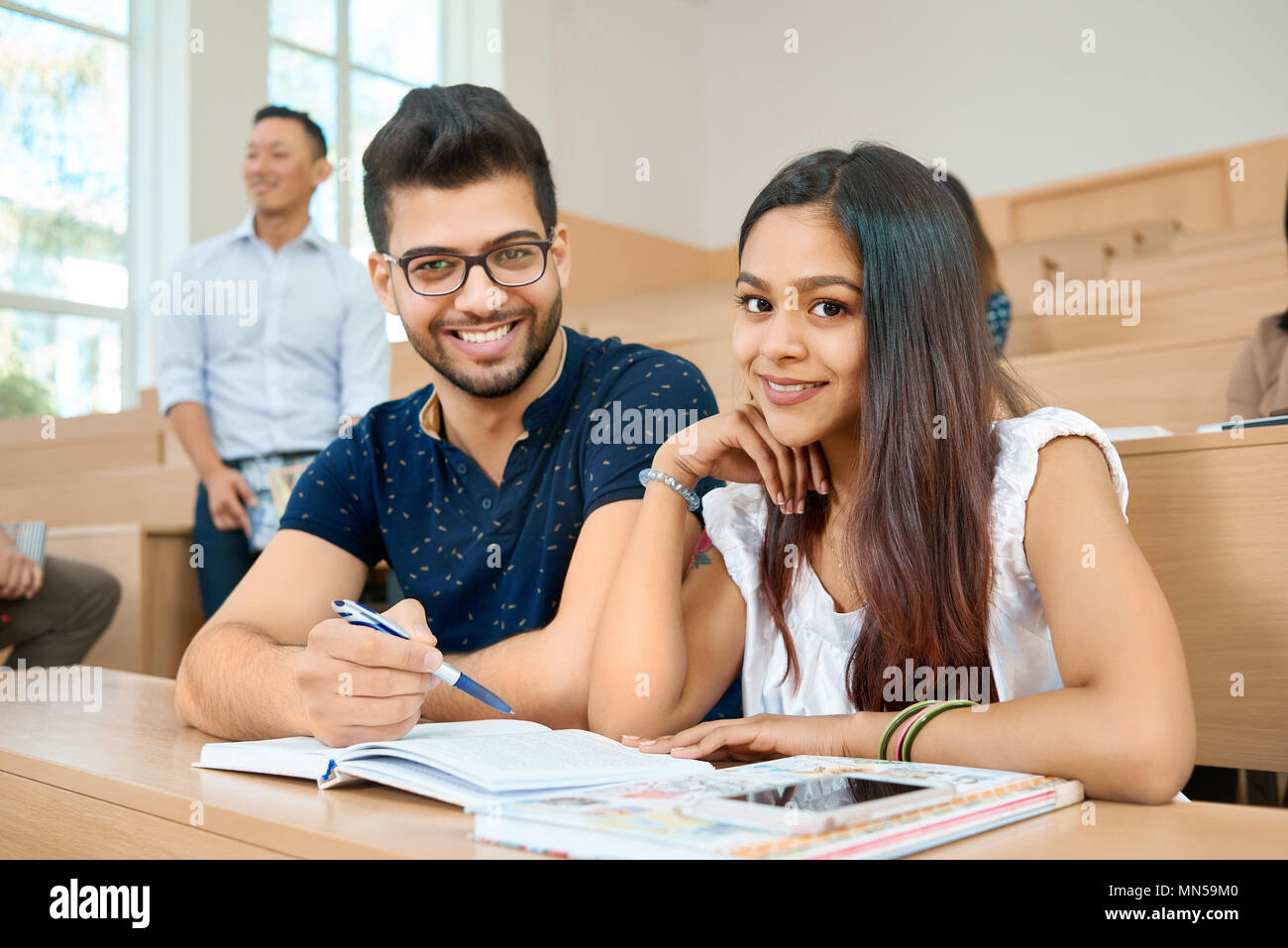 Groupmates coworking for educational scientific project and prepearing for exams, looking at camera in modern spacy university classroom with cascade wooden desks. Looking satisfied, concentrated. - Stock Image