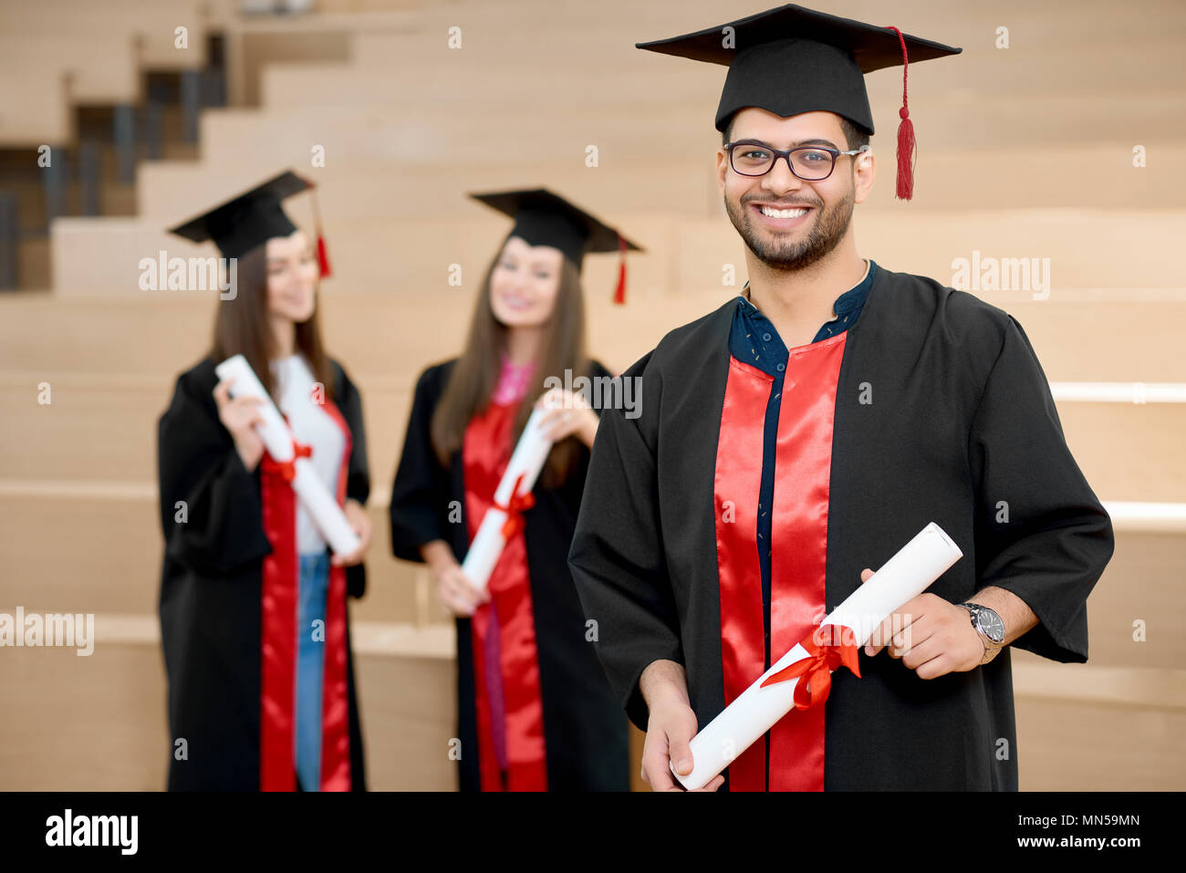 Happy smiling boy keeping university diploma. Graduate standing near young groupmates and looking satisfied. Students wearing black and red colored graduation gowns. Ending university. - Stock Image