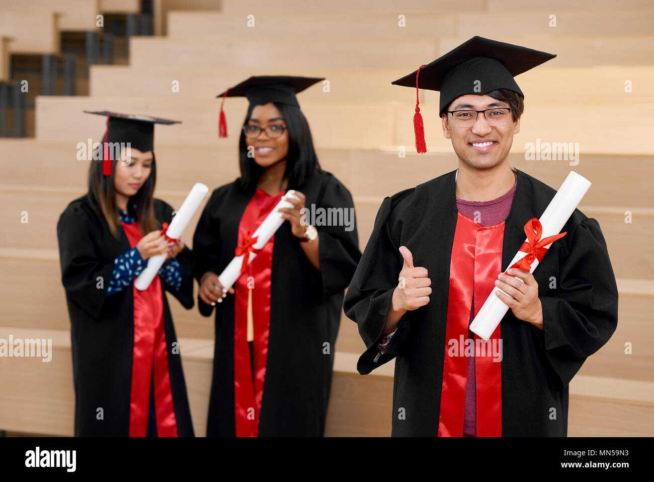 64929f93d6 Smiling different nationalities graduates holding diplomas standing ...
