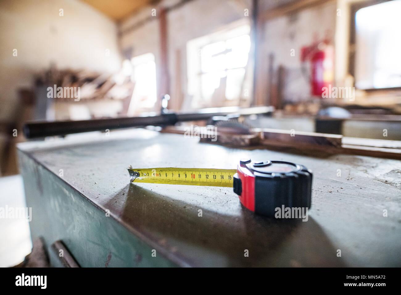 Aflexible ruler in carpentry workshop. Blurred background. - Stock Image