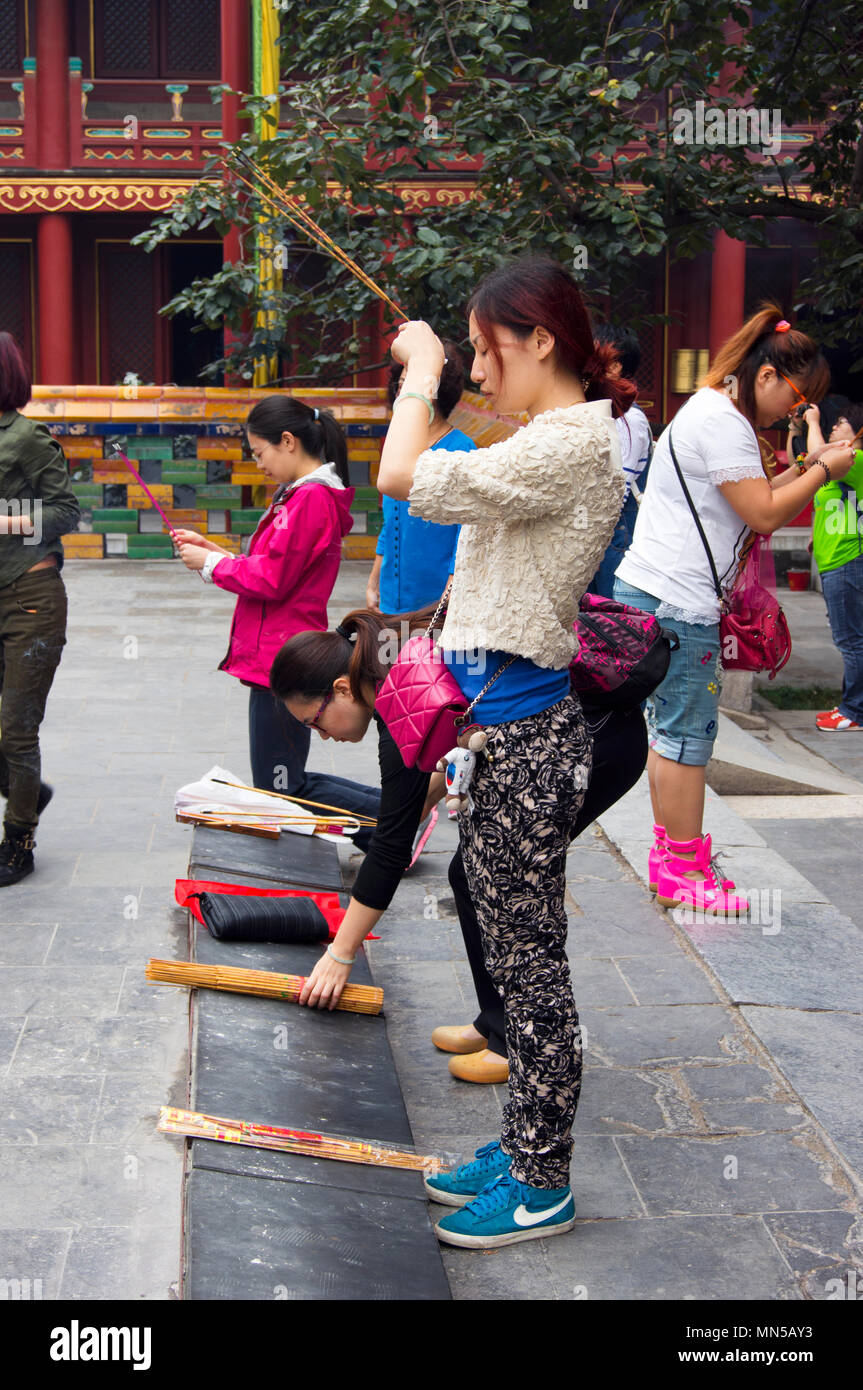 Chinese women praying with incense sticks at a shrine at the