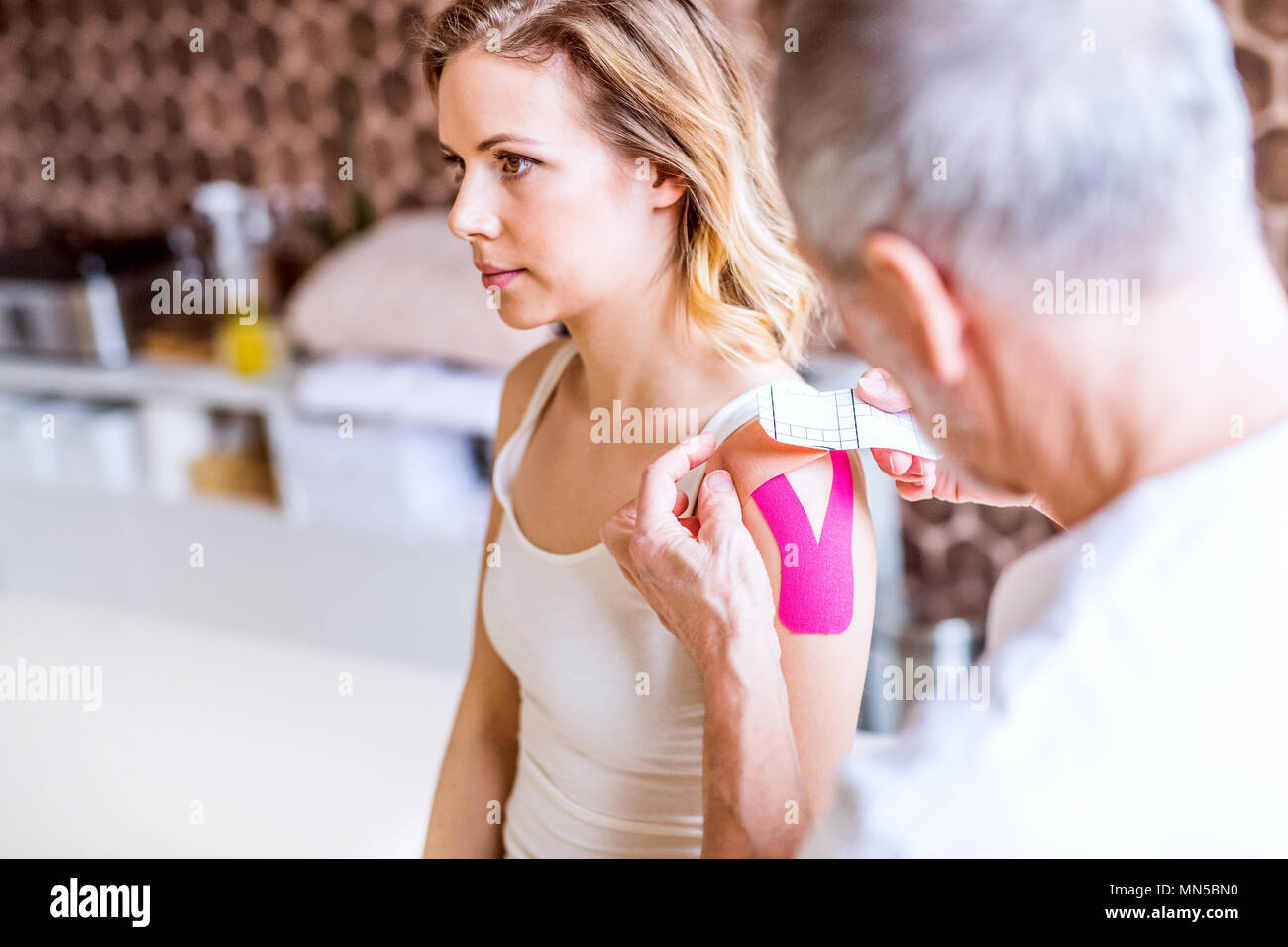 An unrecognizable male physiotherapist applying tape on a young female patient. Close up. - Stock Image