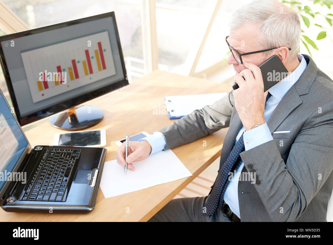 High angle shot of senior investment businessman wearing suit while sitting at office desk in front of laptop and making call. - Stock Image