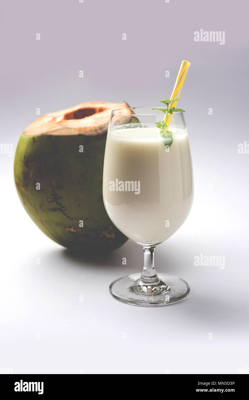 coconut flavoured plain white lassi OR milk shake garnished with a coconut and mint leaves. Selective focus - Stock Image