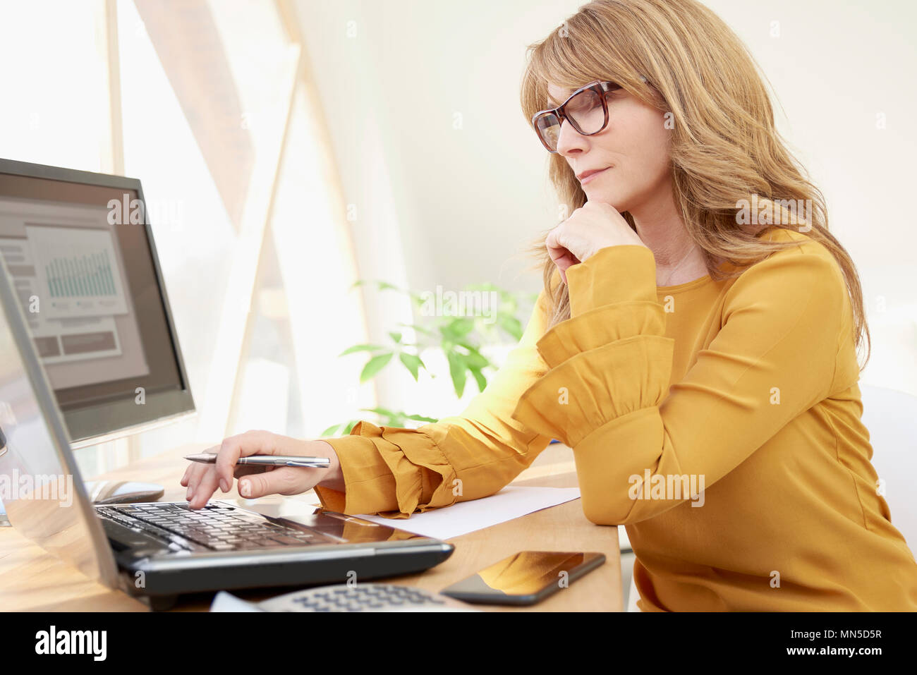 Middle aged casual investment advisor businesswoman working on laptop while sitting at office desk. - Stock Image