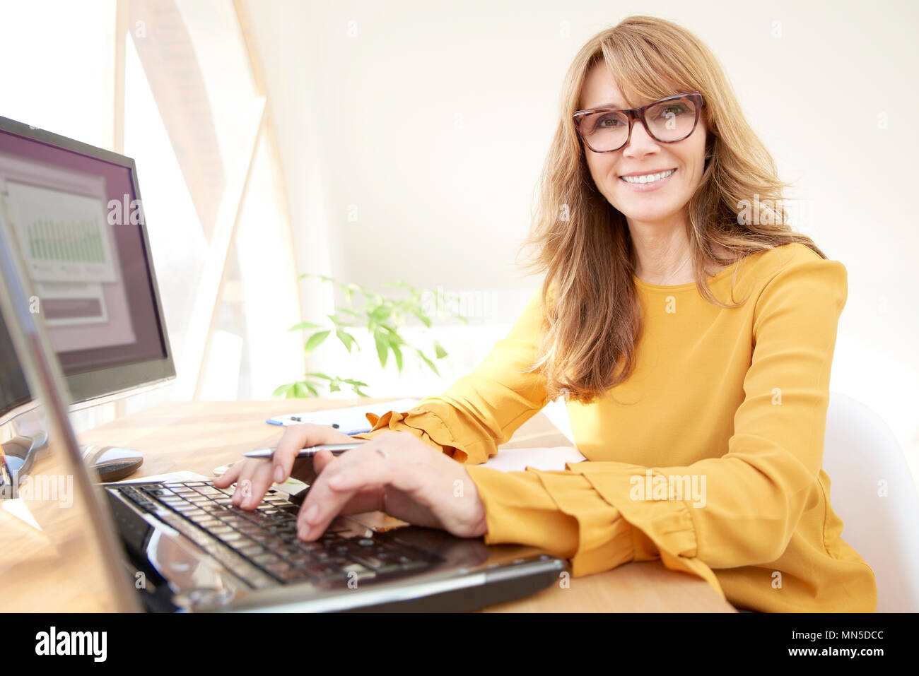 Portrait of a smiling middle aged businesswoman typing on laptop while sitting at desk and looking at camera. Home office. - Stock Image
