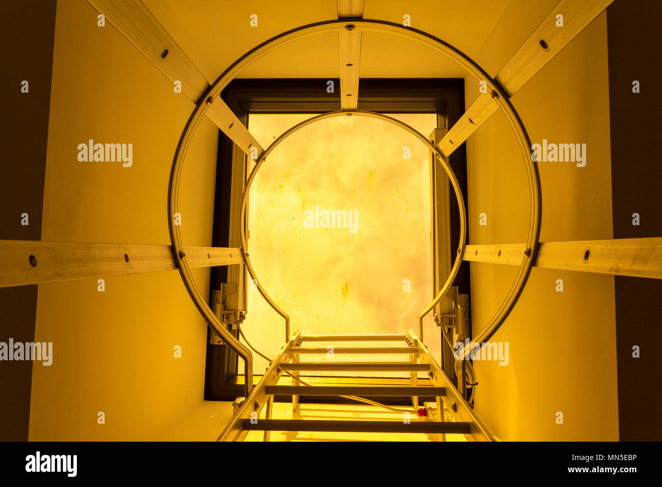 steel hooped ladder leading up onto a building roof, with a perspex clear cover letting the sunset light in. - Stock Image