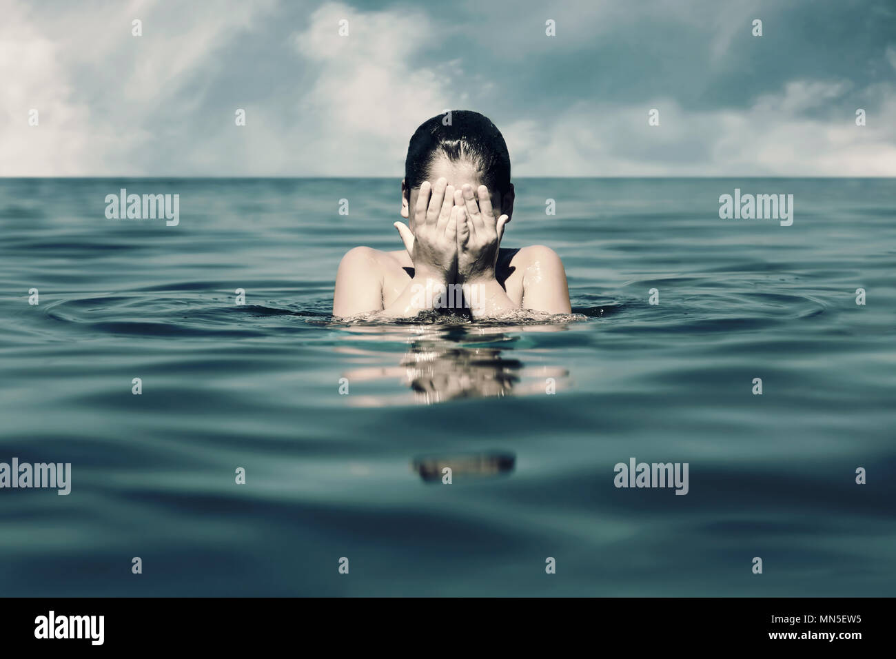 Caucasian little boy covers his face with his hands in the sea. Concept of child abuse, depression, and loneliness. - Stock Image