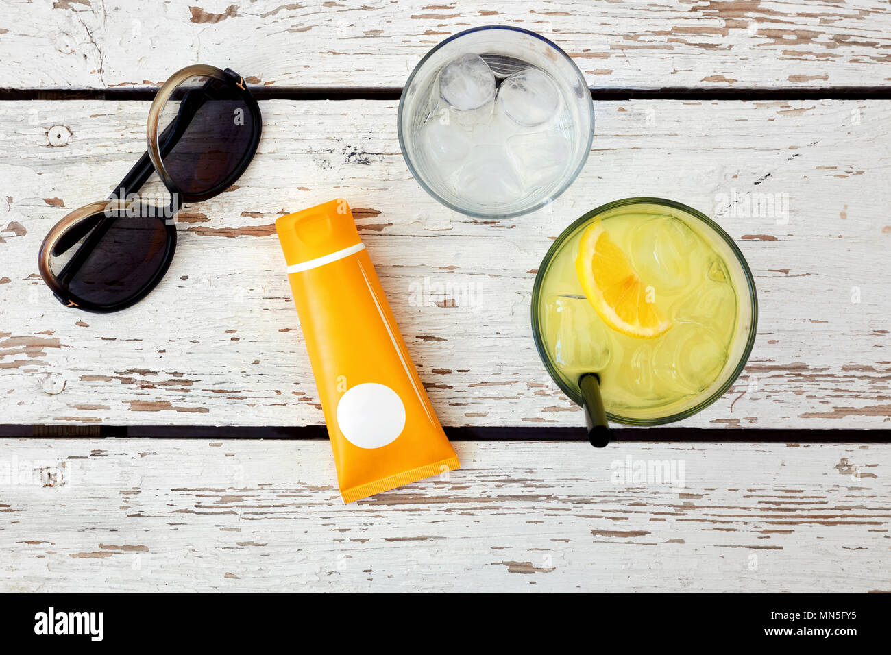 Top view of sunglasses, sunblock, glass of lemonade and water on a white wooden table. Concept of beach accessories and holiday - Stock Image