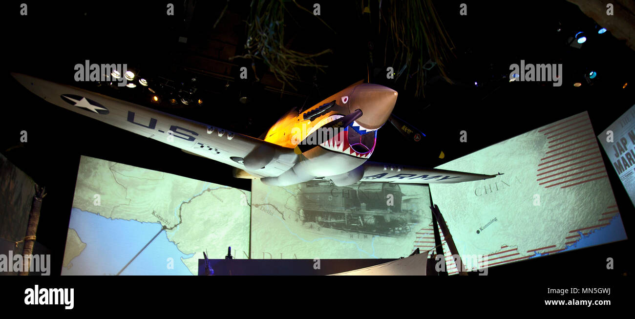 A massive shark-faced P-40 War Hawk fighter hovers above giant video screens showing images from the war-time supply routes over the Himalaya Mountain - Stock Image