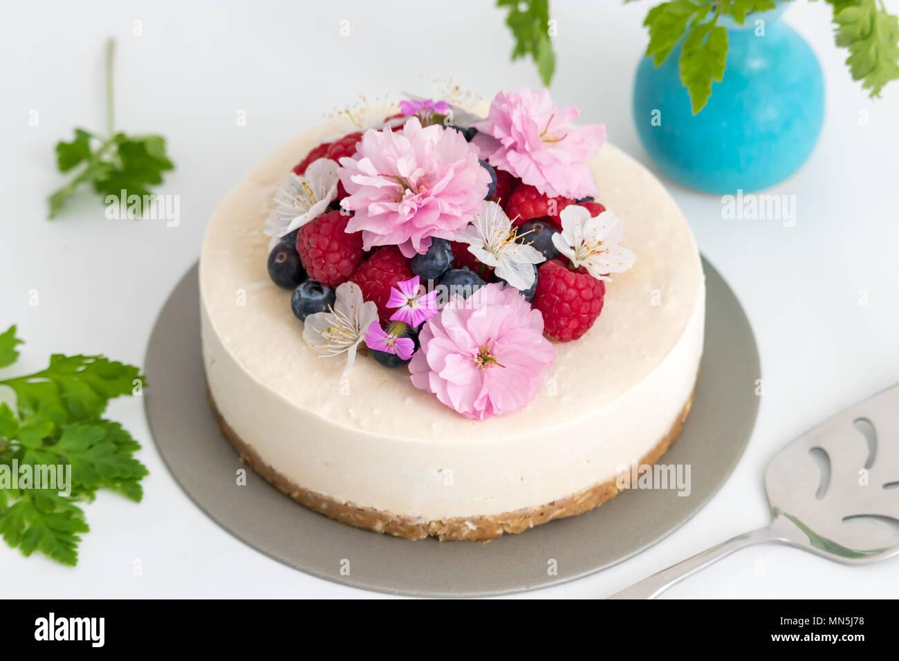This Homemade Raw Cake Is Decorated With Raspberries Blueberries And Fresh Flowers Makes A Delicious Dessert