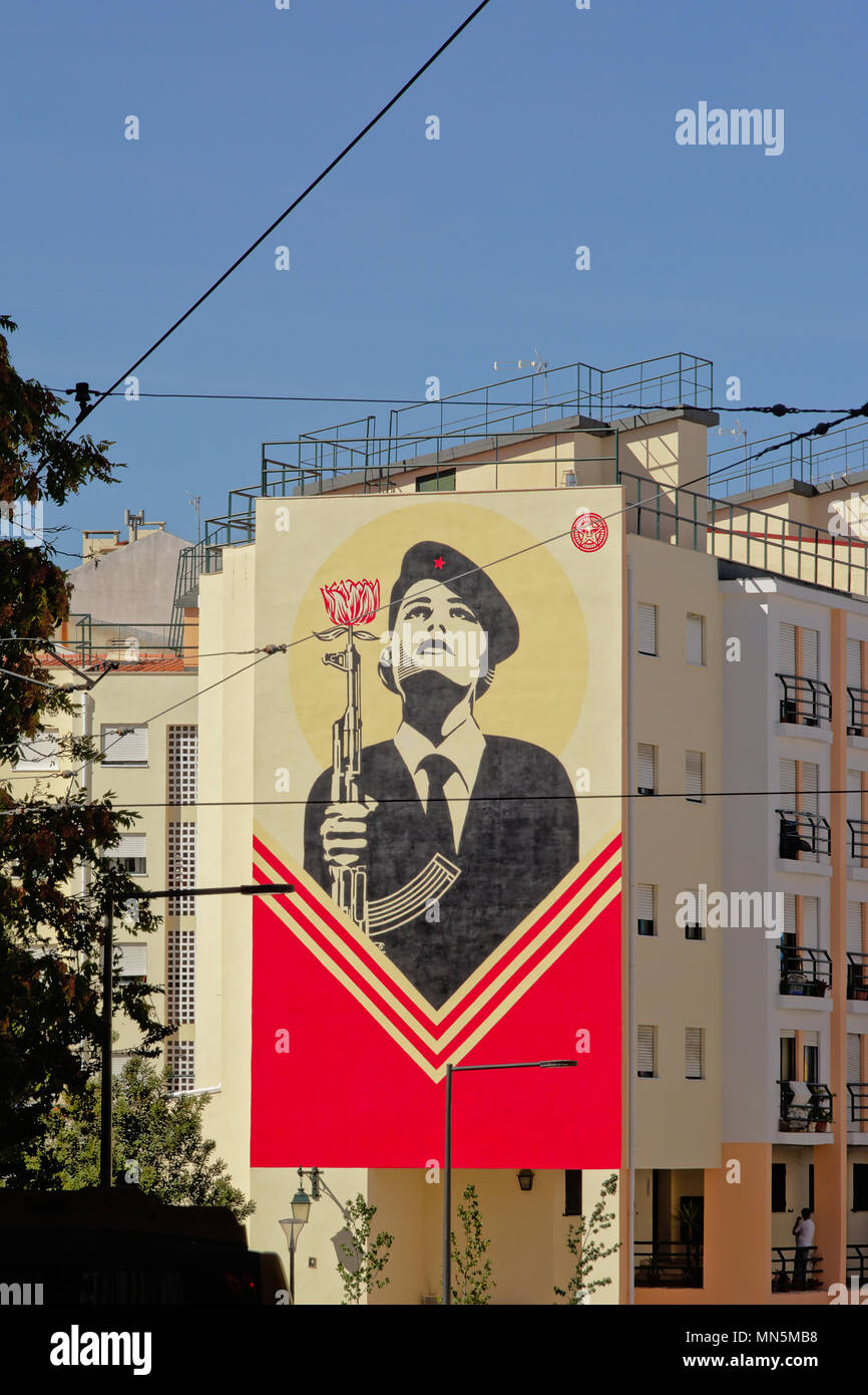 Sreet art as memorial of the Portuguese Carnation Revolution. Women soldier with a gun with a carnation flower in it  on an apartment building in Lisb Stock Photo