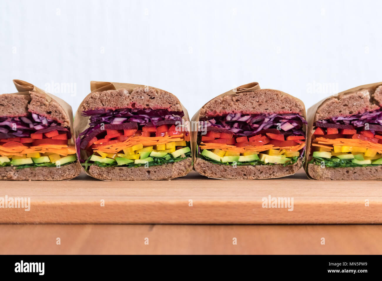 Rainbow salad sandwiches with homemade buckwheat bread, displayed on a wooden board. This fresh healthy lunch is low calorie, dairy free & gluten free. - Stock Image