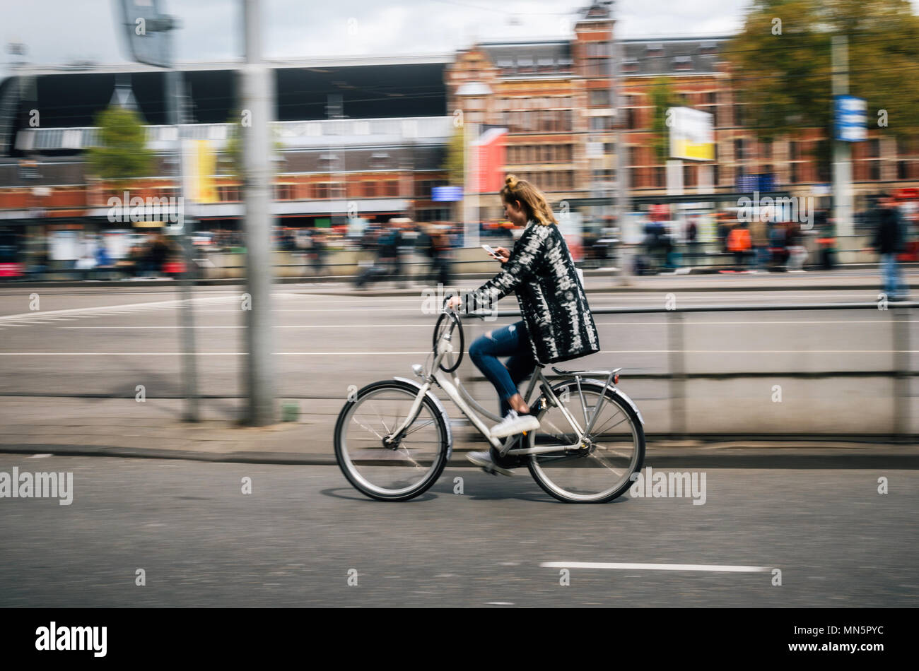 Amsterdam, Netherlands - 27 April, 2017: Young woman rides bicycle and looks in mobile phone holding in one hand. Street of Amsterdam, Netherlands. Mo - Stock Image