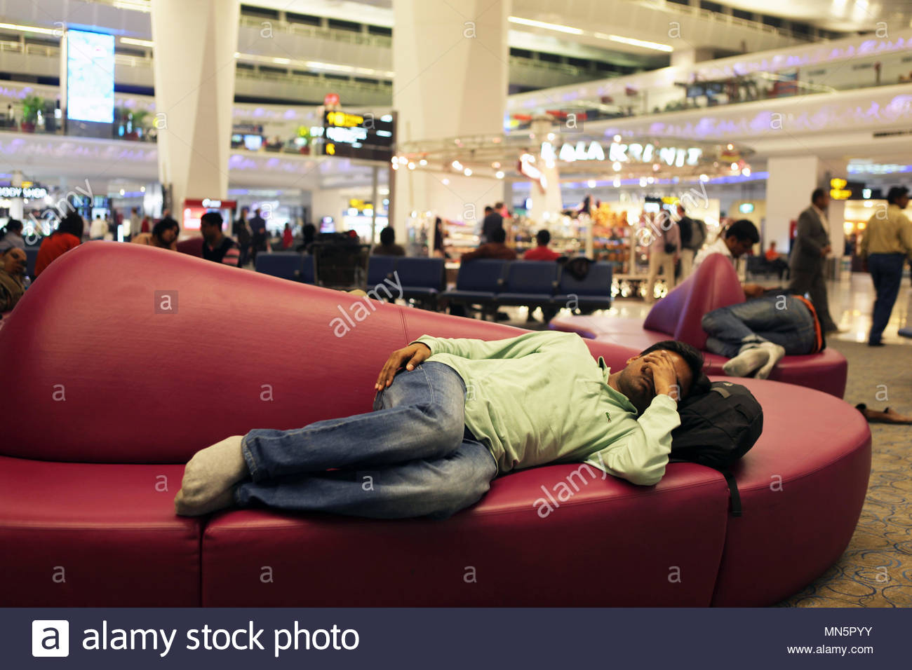 A young man takes a nap at around 3 AM while waiting for an early morning flight in the recently renovated terminal 3 at Indira Gandhi International A - Stock Image