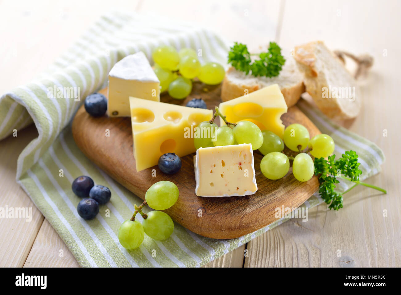Cheese snack with serveral kinds, served with bread and grapes on a wooden cutting board - Stock Image
