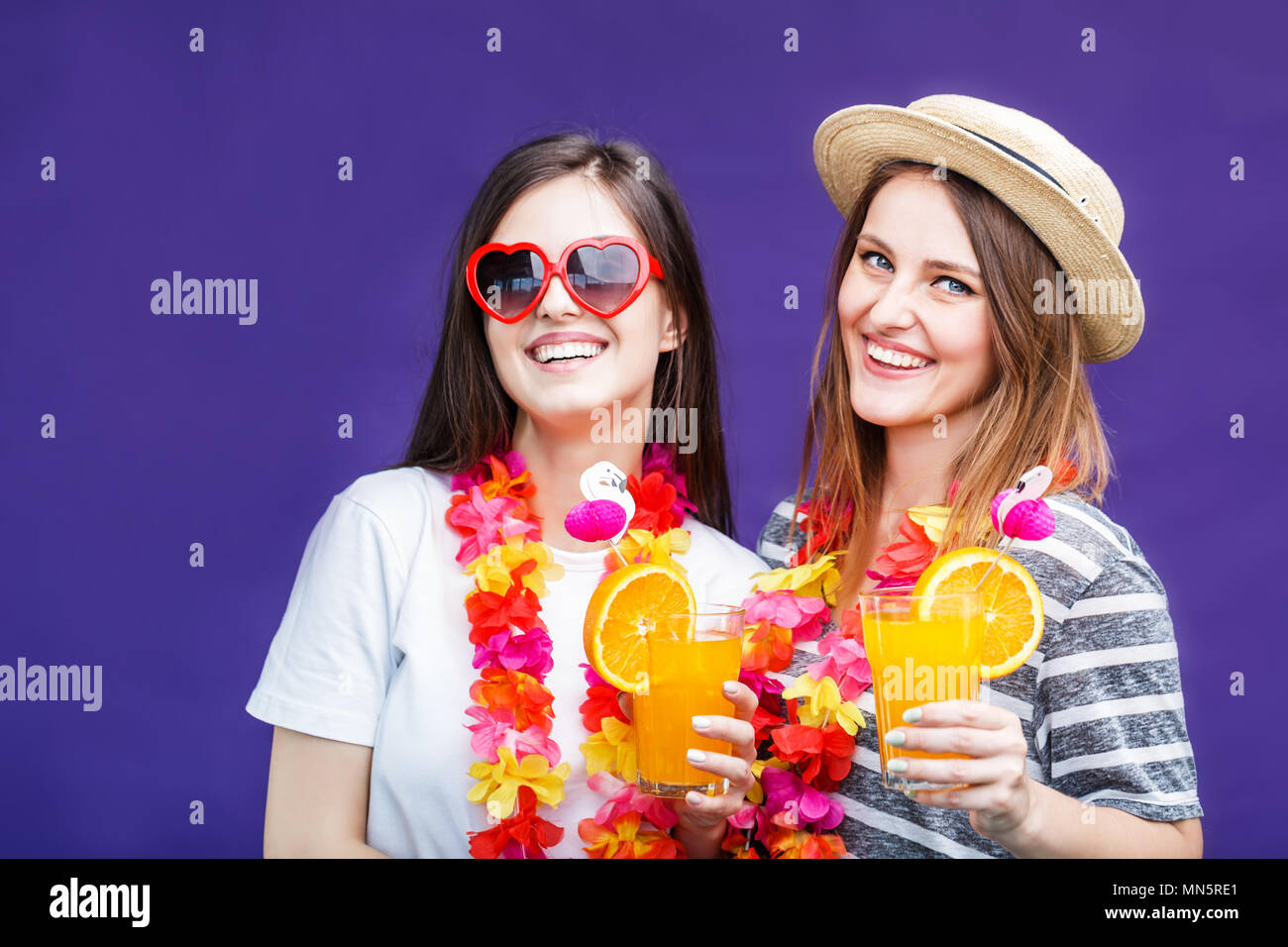 Two pretty smiling girls with lei on neck holds orange drinks before purple background - Stock Image