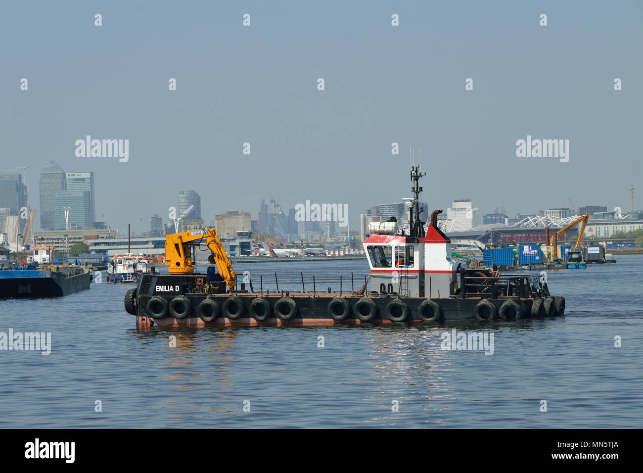 Boats and barges in the King George V Dock in London's Royal Docks working on the London City Airport Development Programme (CADP) construction site Stock Photo