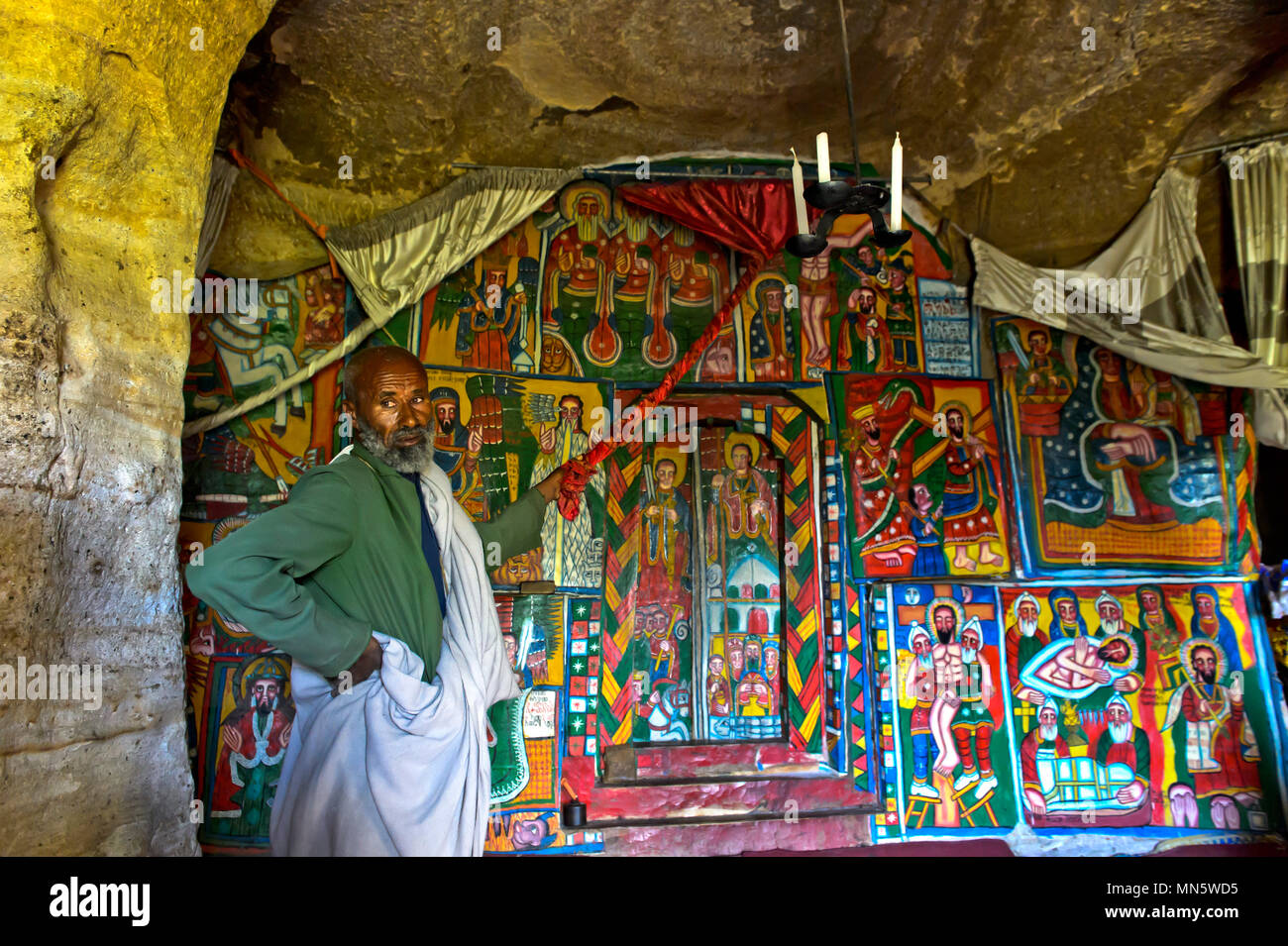 Priest shows canvas paintings with biblical motifs in the interieur of the rock-hewn church Mikael Mellehayzengi, Tsaeda Amba, Tigray, Ethiopia - Stock Image