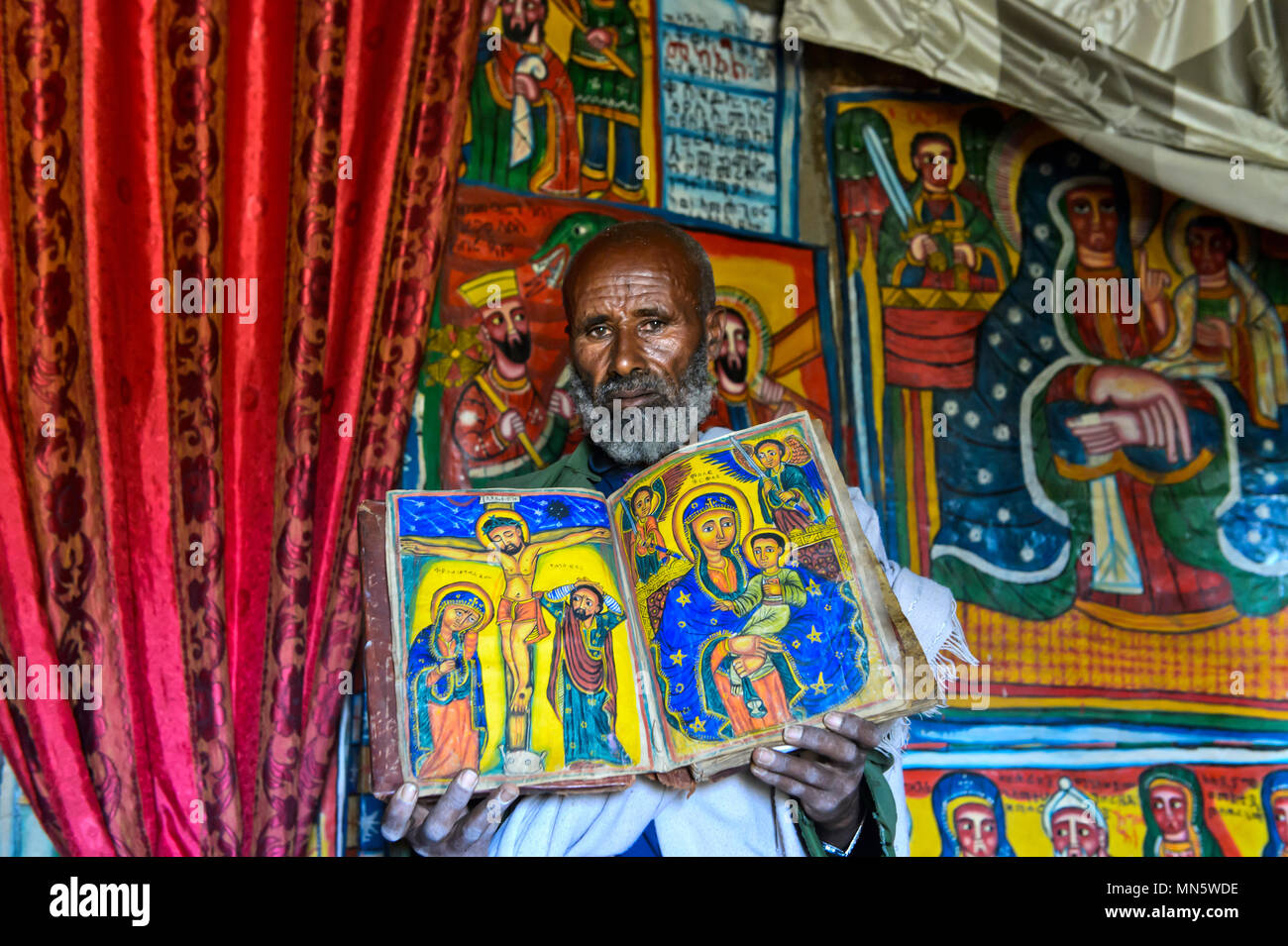 Priest of the rock-hewn church Mikael Mellehayzengi showing the book Miracles of Maria with colorful hand-painted designs on parchment,Ethiopia - Stock Image