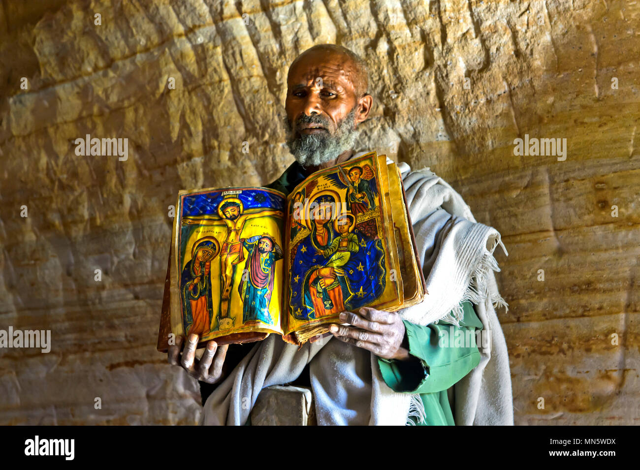 Priest of the rock-hewn church Mikael Mellehayzengi showing the book Miracles of Maria with colorful hand-painted designs on parchment,Tigray,Ethiopia - Stock Image