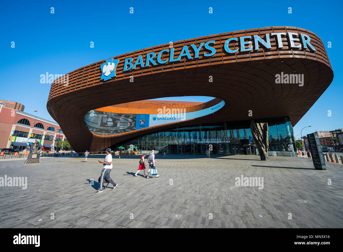 NEW YORK CITY - AUGUST 30, 2016: Pedestrians pass under the distinctive architecture of the Barclays Center, a  sports and entertainment arena Stock Photo