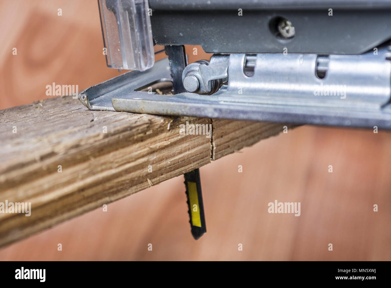 Cutting wood plank with jigsaw electric tool. Saw Blade in plank. Close up, selective focus. Stock Photo