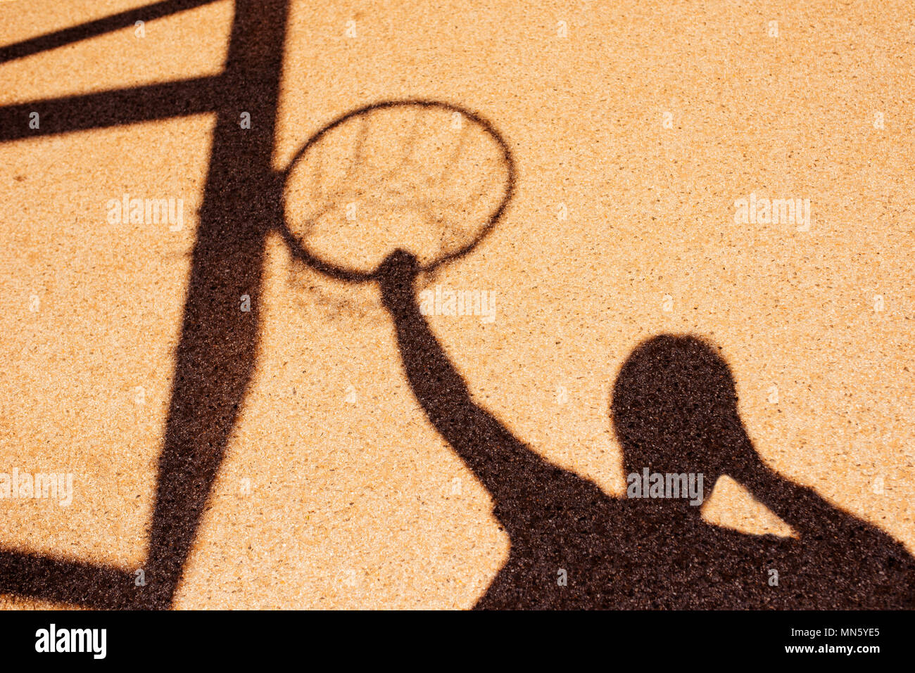 Shadow of male basketball player in slam dunk pose, holding the hoops - Stock Image