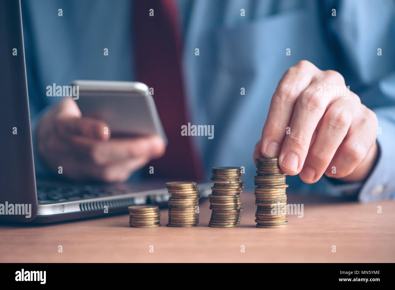 Businessman using smartphone with stacked coins in foreground, close up shot with selective focus - Stock Image