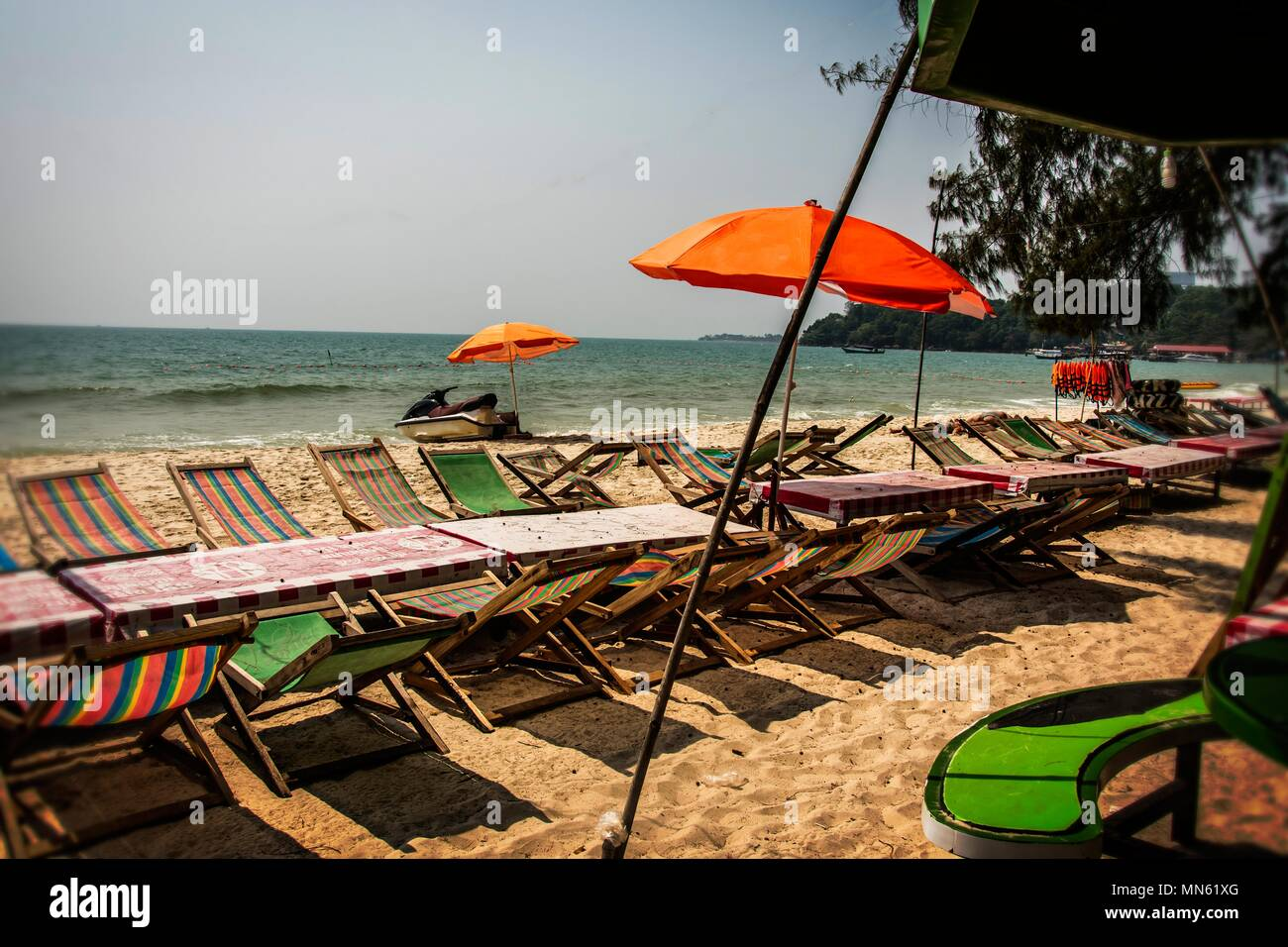 sunbeds and umbrellas on the ochheuteal tourist beach in the vicinity of the port and city of Sihanoukville. Cambodia - Stock Image
