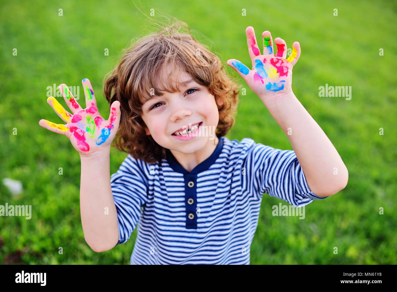 boy with curly hair without front milk tooth shows hands dirty with multi-colored finger paints and smiles. - Stock Image