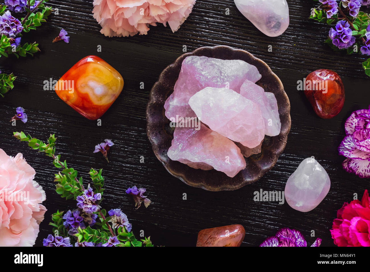 Rose Quartz and Carnelian on Dark Table with Carnations and Sea Lavender - Stock Image