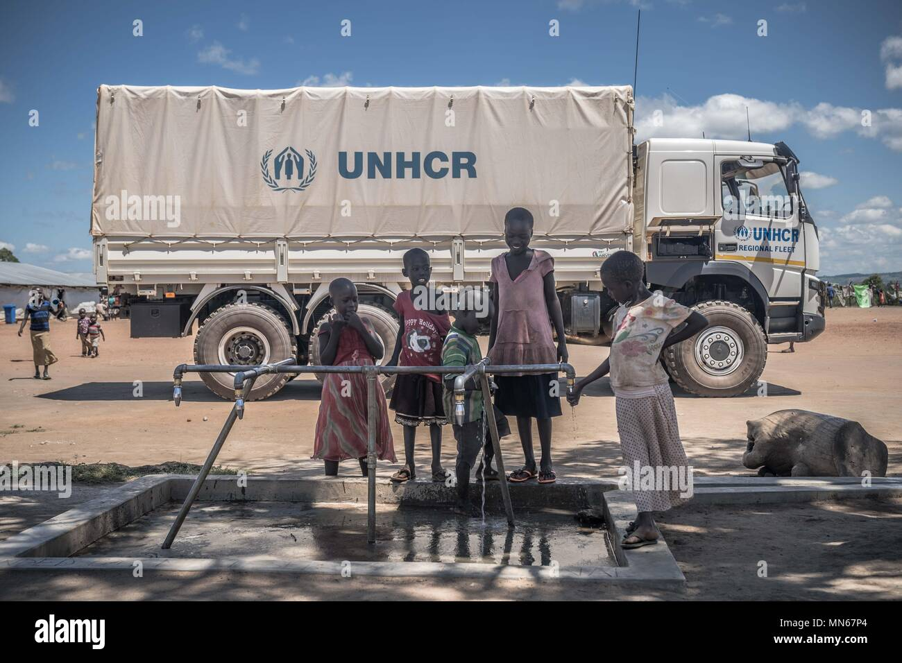 394f6b60aa2 Young South Sudanese refugees seen getting water at a public water tap in  front of a UNHCR truck which took them here just few hours ago. The Kuluba  refugee ...
