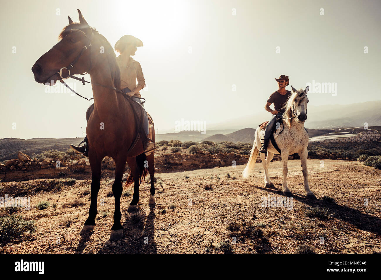 couple of horses and cowboys male and female ride free in the nature at the mountains in tenerife. lifestyle and alternative works or leisure activity - Stock Image