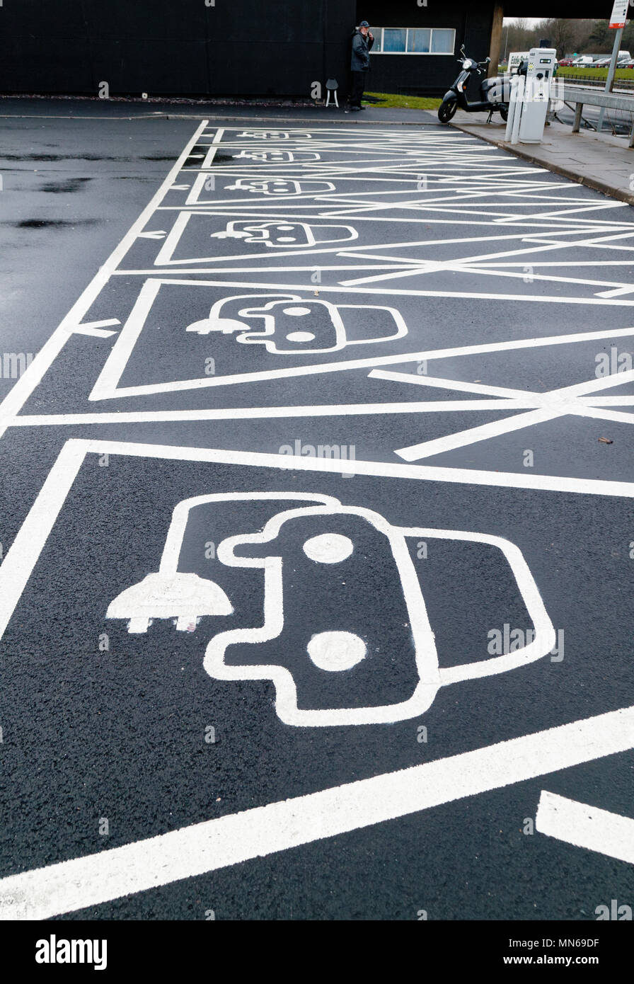 Electric vehicle plug in places in a motorway services car park in England - Stock Image